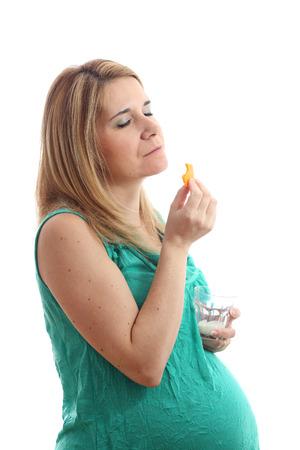 Los detalles de una mujer embarazada con un vaso de leche y queso aislados sobre fondo blanco. Foto de archivo