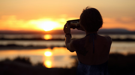 Details of a woman is photographing a beautiful sunset in summer