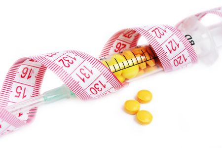 illustrating: Syringe full with pills wrapped in tape measure illustrating wrong dieting and drug abuse Stock Photo