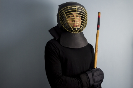 An eskrimador with stick and protective helmet and gloves Stock Photo - 17725527