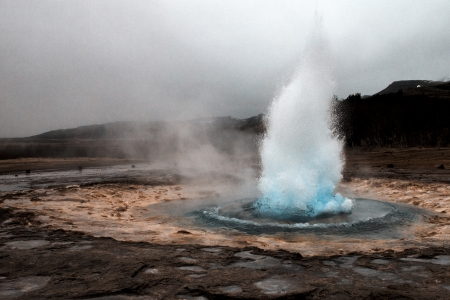 Geyser erupting in geothermal field Stock Photo