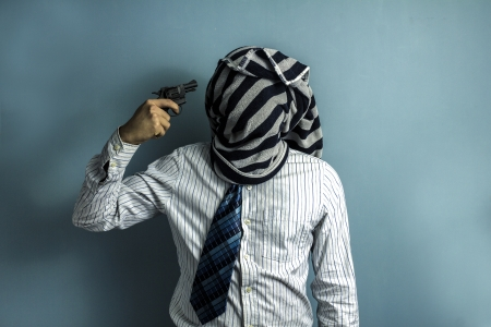 A man with a towel areound his head pointing a gun at himself photo