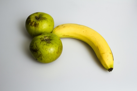 Two apples and a banana arranged in a suggestive manner Stock Photo - 19904297