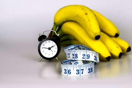 get in shape: Banana, clock and tape measure Stock Photo