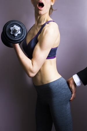 groping: Fit young woman being groped while working out Stock Photo
