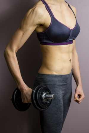 Athletic female with dumbbell photo