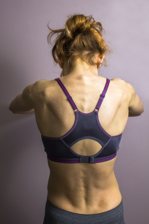 Athletic woman stretching her back photo