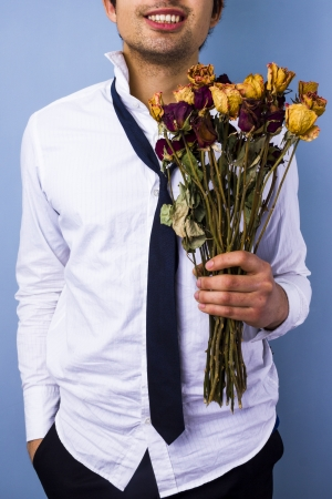 unrecognisable person: Messy young man with dead flowers, bad boyfriend