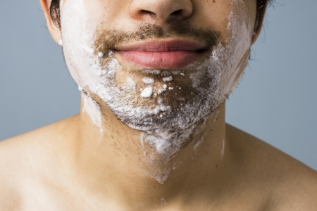 Young multiracial man shaving with foam photo