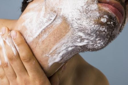 regimen: Young multiracial man shaving with foam