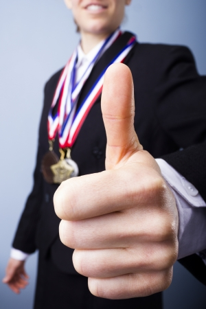unrecognisable person: Award winning businesswoman with medals giving thumbs up Stock Photo