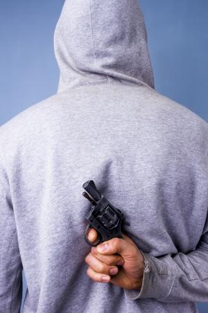 Hooded man hiding gun behind his back