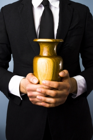Businessman holding a wooden urn Stock Photo
