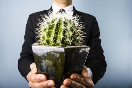 double cross: Uomo che presenta un cactus Archivio Fotografico