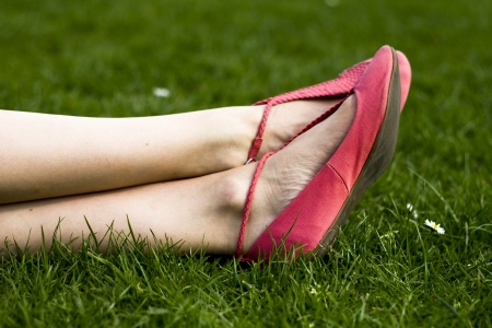Close up on a young woman s feet and shoes on the grass