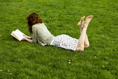 well read: Young woman relaxing with a book on the grass in the park Stock Photo