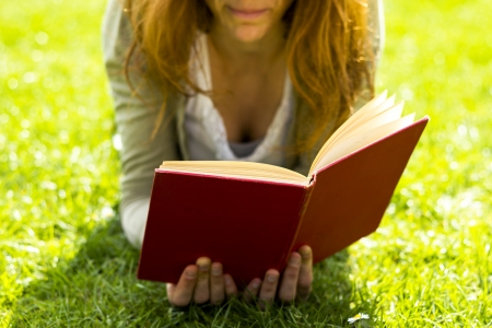 nook: Young woman reading on the lawn in her garden