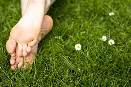 Close up on a young woman s bare feet in the green grass photo