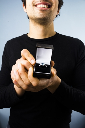 Happy young man presenting an engagement ring photo