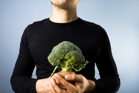 brocolli: Young man holding a head of brocolli Stock Photo