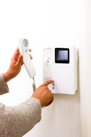 Detail of man answering intercom