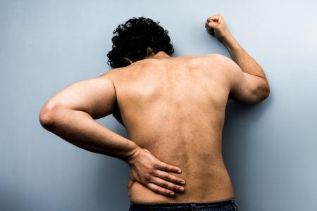 dolor espalda: �tnico hombre joven con dolor de espalda severo y ci�tica