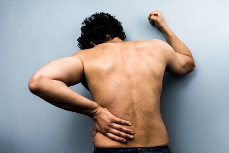 Young ethnic man with severe back pain and sciatica photo