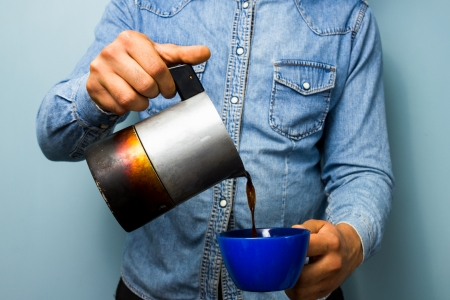 coffee pot: Young worker pouring coffee Stock Photo