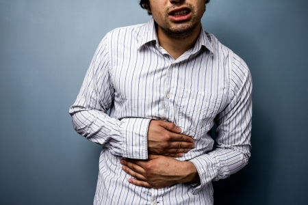 cramps: Young ethnic man with constipation and stomach cramps