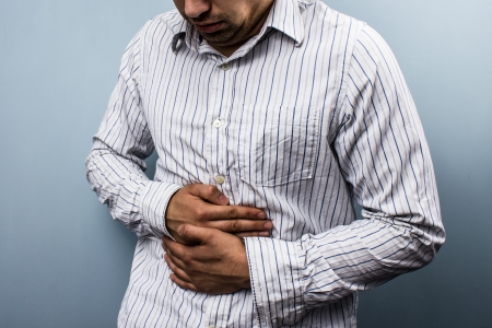 Young multi racial man with stomach pains photo
