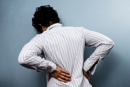 backpain: Rear view of dark haired man with severe back pain Stock Photo