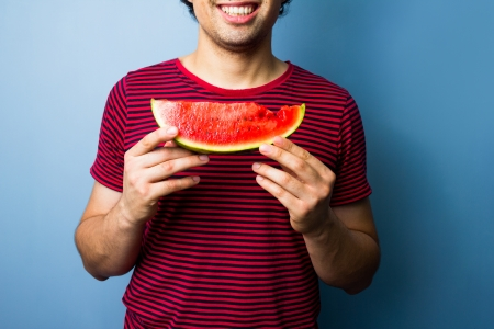 Young man eating water melon Stock Photo