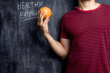 Athletic man with grapefruit promoting healthy eating Stock Photo - 21561751