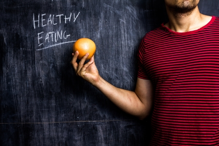 Athletic man with grapefruit promoting healthy eating Stock Photo - 21561758