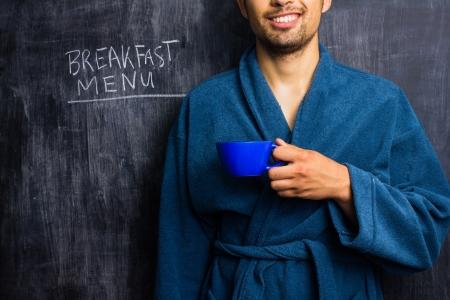 Man in dressing gown in front of blackboard with breakfast menu written on it photo