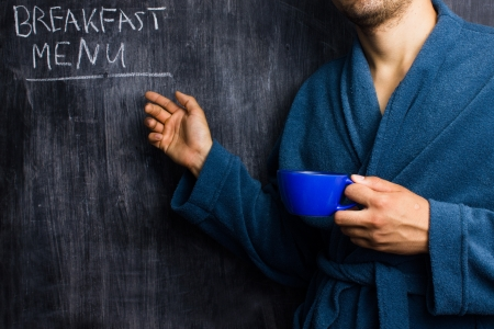 Man in dressing gown pointing to breakfast menu photo
