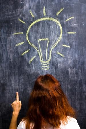 id�e lumineuse: Femme rousse au tableau noir ayant id�e lumineuse Banque d'images