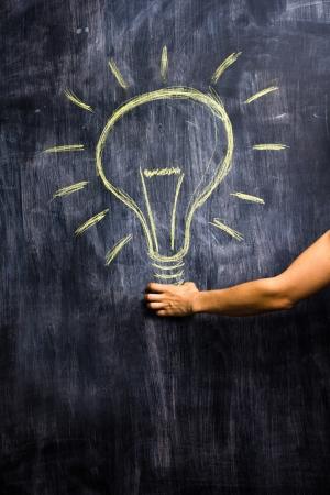 Woman s hand holding a giant lightbulb on blackboard