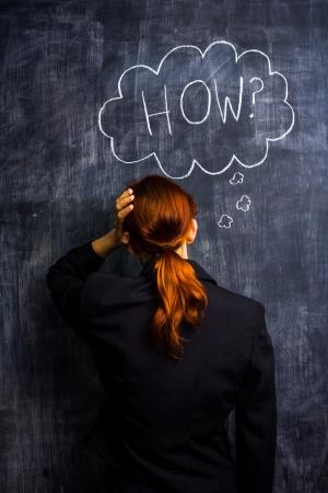 Redhead businesswoman at blackboard asking how photo
