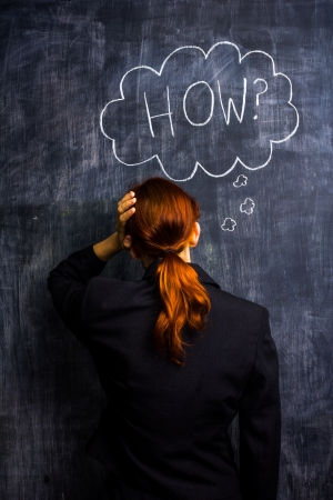 unrecognisable person: Redhead businesswoman at blackboard asking how
