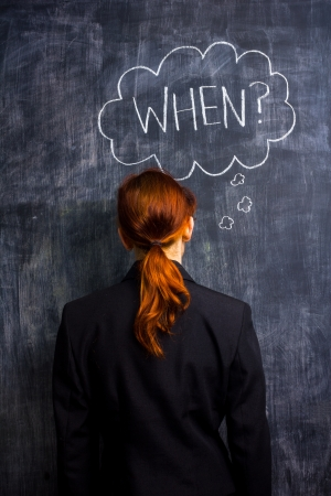unrecognisable person: Redhead businesswoman at blackboard asking when