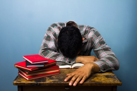 slumped: Man asleep on open book after studying