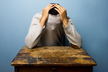 Man at desk hiding in his jumper Stock Photo