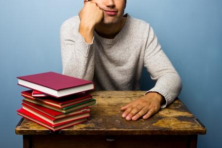 bored man: Uomo annoiato al tavolo con i libri