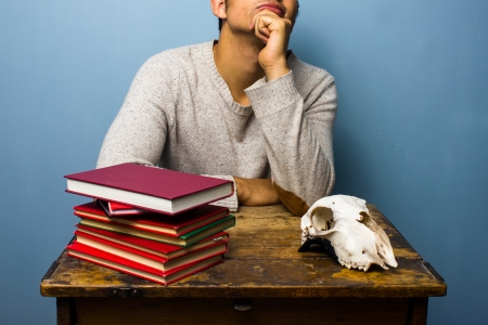 Man at desk with books and goat s skull Banco de Imagens