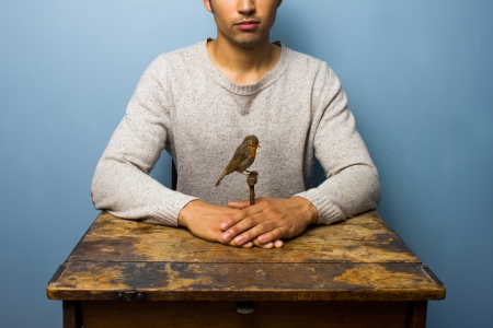 Man at desk with a taxidermy robin photo