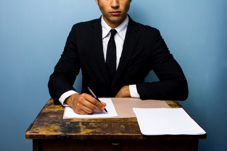Businessman signing papers at old desk photo