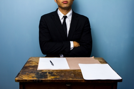 Businessman refusing to sign papers at old desk photo
