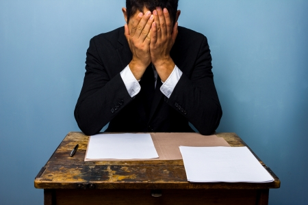 Worried businessman sitting at an old desk with documents in front of him photo
