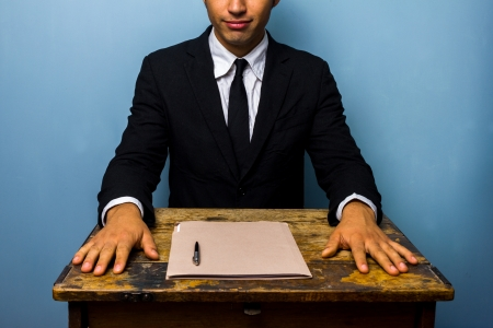 Businessman sitting at an old desk with documents in front of him photo